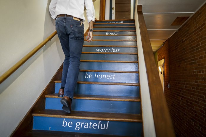 "Michael Koveleski climbs the stairs at his store Design Sleepin Yellow Springs, Ohio on Thursday, Aug. 23, 2018. ""You're only going to change your life when things are bad - or terrible,"" Michael says. ""Our thing was 9/11, starting over with nothing. ... I am thrilled at the way it came out to be."" (AP Photo/John Minchillo)"
