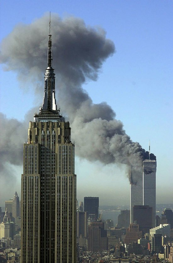 In this Tuesday, Sept. 11, 2001 file photo, plumes of smoke rise from the World Trade Center buildings in New York. The Empire State building is seen in the foreground. (AP Photo/Patrick Sison)