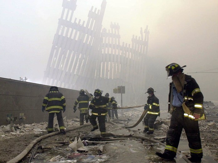 In this Tuesday, Sept. 11, 2001 file photo, with the skeleton of the World Trade Center twin towers in the background, New York City firefighters work amid debris on Cortlandt St. after the terrorist attacks. (AP Photo/Mark Lennihan)