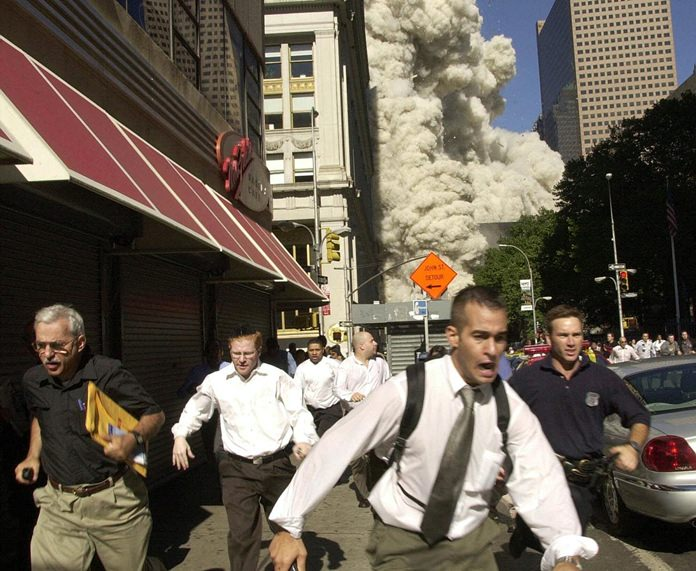 In this Tuesday, Sept. 11, 2001 file photo, people run from a cloud of debris from the collapse of a World Trade Center tower in New York. (AP Photo/Suzanne Plunkett)