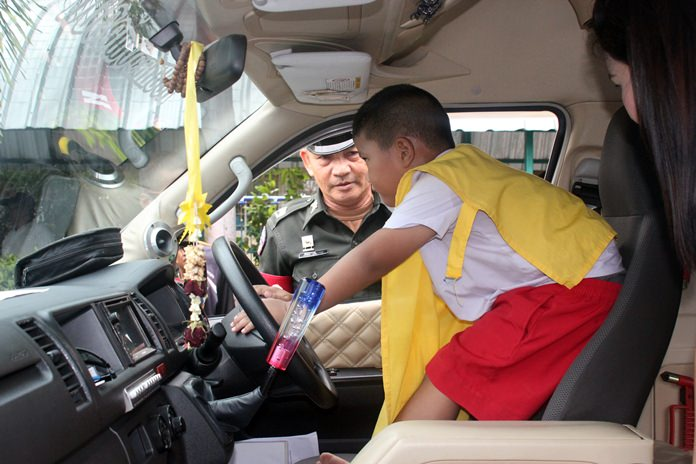 Traffic Pol. Maj. Aruth Sapanon teaches a child how to honk the horn to call for help.