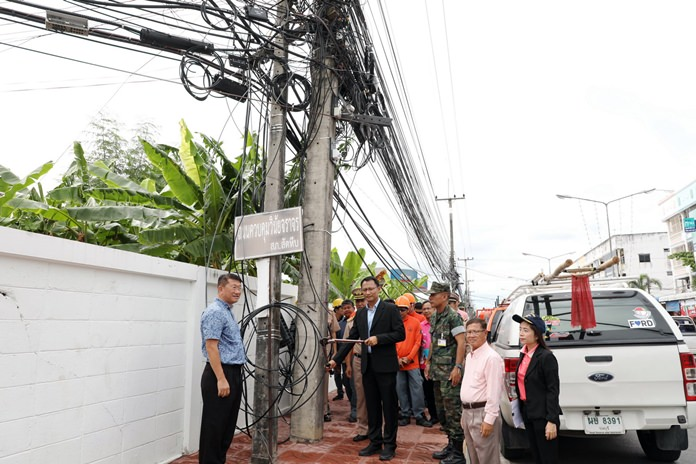 District Chief Auncha Intasorn and Sattahip Mayor Narong Bunbancherdsri pose for the cameras with wire cutters to begin tidying up chaotic power, television and internet lines in the city's most-popular areas.