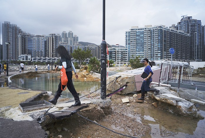 People walk past debris caused by Typhoon Mangkhut outside a housing estate on the waterfront in Hong Kong, Monday, Sept. 17. (AP Photo/Vincent Yu)