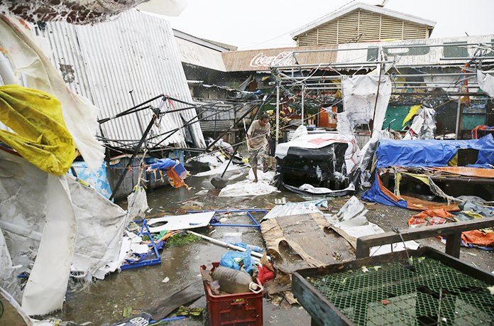 Residents walk along destroyed stalls at a public market due to strong winds Saturday, Sept. 15, as Typhoon Mangkhut barreled across Tuguegrao City in Cagayan province, northeastern Philippines. (AP Photo/Aaron Favila, File)