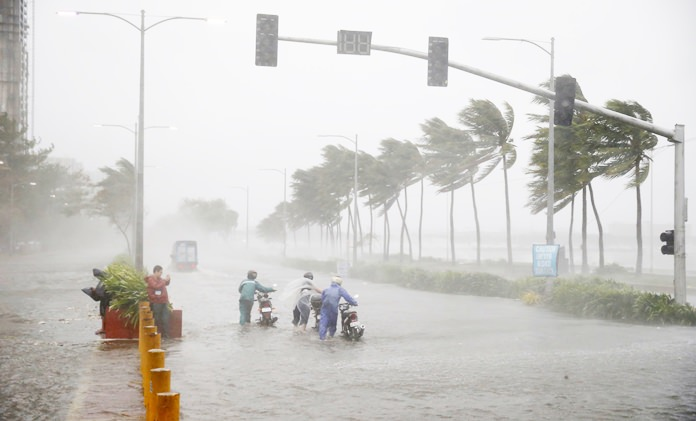 Motorists brave the rain and strong winds brought about by Typhoon Mangkhut which barreled into northeastern Philippines before dawn Saturday, Sept. 15, in Manila, Philippines. Nature expresses its fury in sundry ways. Two deadly storms - Hurricane Florence and Typhoon Mangkhut - roared ashore on the same day, half a world apart, but the way they spread devastation was as different as water and wind. (AP Photo/Bullit Marquez)