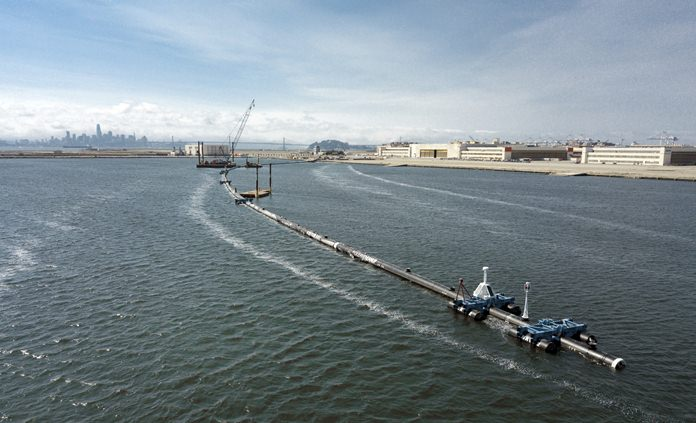 In this Monday, Aug. 27, 2018 photo provided by The Ocean Cleanup, a long floating boom that will be used to corral plastic litter in the Pacific Ocean is assembled in Alameda, Calif. (The Ocean Cleanup via AP)
