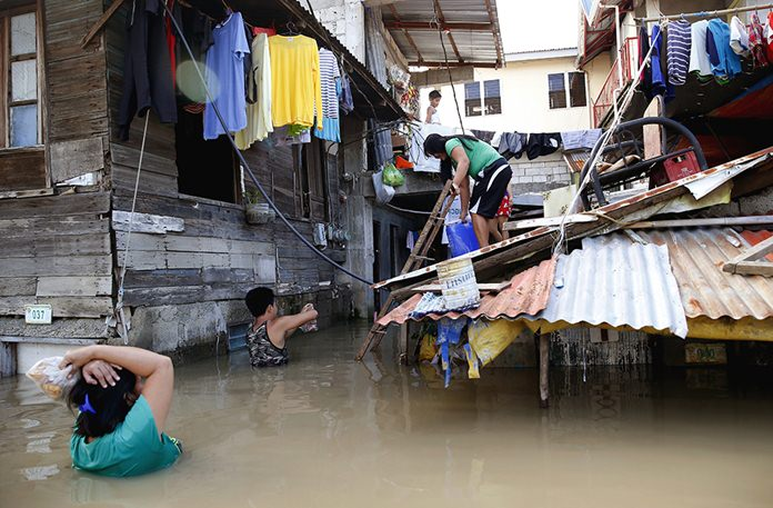 A couple wades through floodwaters to buy drinking water following flooding brought about by Typhoon Mangkhut which barreled into northeastern Philippines and inundated low-lying areas in its 900-kilometer wide cloud band in Calumpit township, Bulacan province north of Manila, Philippines. (AP Photo/Bullit Marquez, File)