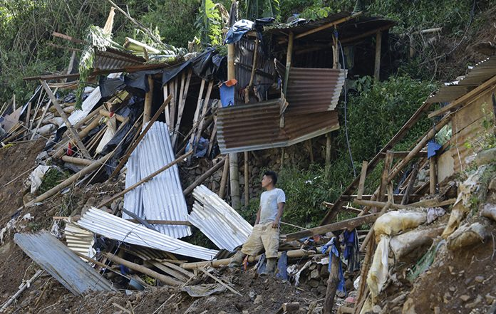 A resident stands beside toppled houses at the site where victims are believed to have been buried by a landslide after Typhoon Mangkhut lashed Itogon, Benguet province, northern Philippines. (AP Photo/Aaron Favila, File)