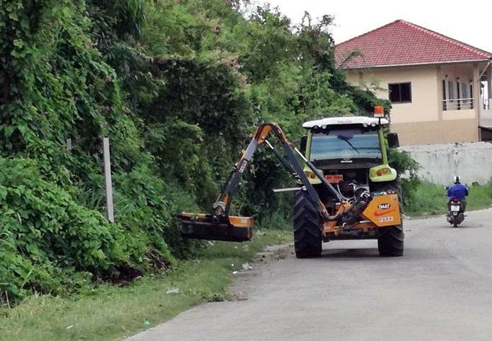"""Nongprue workers prune trees and mow weeds at the Marbtato """"little hill"""" intersection."""