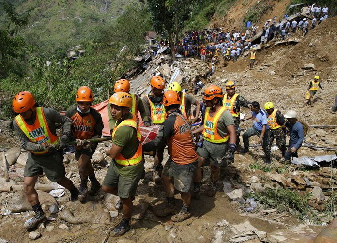 Rescuers carry a body recovered from a landslide caused by Typhoon Mangkhut in Itogon, Benguet province, northern Philippines on Monday, Sept. 17. (AP Photo/Aaron Favila)