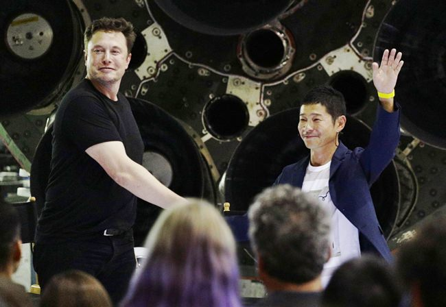 SpaceX founder and chief executive Elon Musk, left, shakes hands with Japanese billionaire Yusaku Maezawa, right, after announcing him as the first private passenger on a trip around the moon, Monday, Sept. 17, in Hawthorne, Calif. (AP Photo/Chris Carlson)