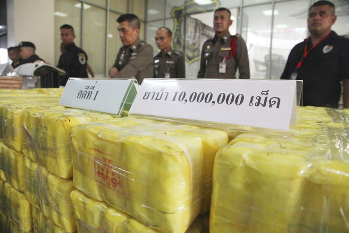 Policemen stand in front of seized methamphetamine pills at the Narcotics Suppression Bureau during a press conference in Bangkok, Tuesday, Sept. 18. (AP Photo)