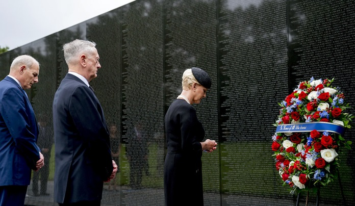 Cindy McCain, wife of, Sen. John McCain, R-Ariz., accompanied by White House Chief of Staff John Kelly, left, and Defense Secretary Jim Mattis, second from left, lays a wreath at the Vietnam Veterans Memorial in Washington, Saturday, Sept. 1, 2018, during a funeral procession to carry the casket of her husband from the U.S. Capitol to National Cathedral for a memorial service. McCain served as a Navy pilot during the Vietnam War and was a prisoner of war for more than five years. (AP Photo/Andrew Harnik, Pool)