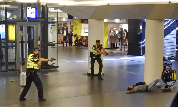 Dutch police officers point their guns at a wounded 19-year-old man who was shot by police after stabbing two people in the central railway station in Amsterdam, the Netherlands, Friday Aug. 31, 2018. (AP Photo)