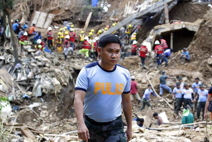 In this Tuesday, Sept. 18, 2018, file photo, Philippine Police Senior Inspector Heherson Zambale walks at the site where victims were buried in a landslide set off by Typhoon Mangkhut as it lashed across Itogon, Benguet province, northern Philippines. (AP Photo/Aaron Favila)
