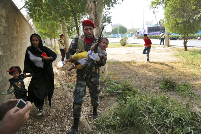 An Iranian soldier carries away a child from a shooting scene during a military parade marking the 38th anniversary of Iraq's 1980 invasion of Iran, in the southwestern city of Ahvaz, Iran, Saturday, Sept. 22. (AP Photo/Mehr News Agency, Mehdi Pedramkhoo)