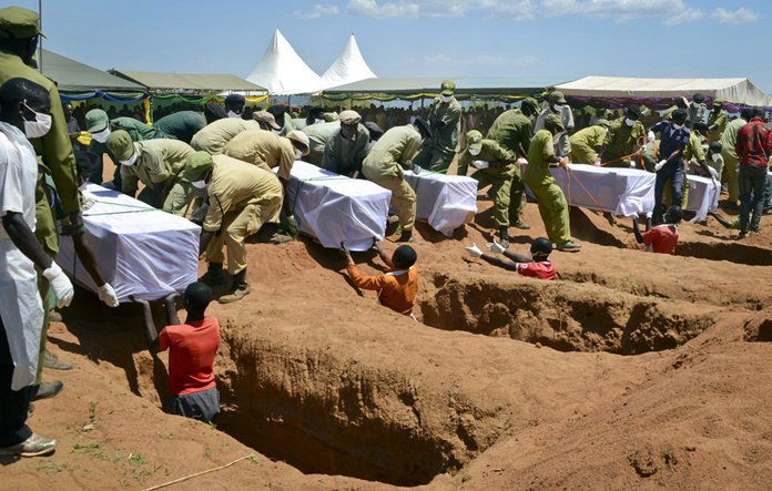 Coffins of some of the victims of the MV Nyerere passenger ferry capsizing are laid into graves during a mass burial ceremony on Ukara Island, Tanzania, Sunday, Sept. 23. (AP Photo/Andrew Kasuku)