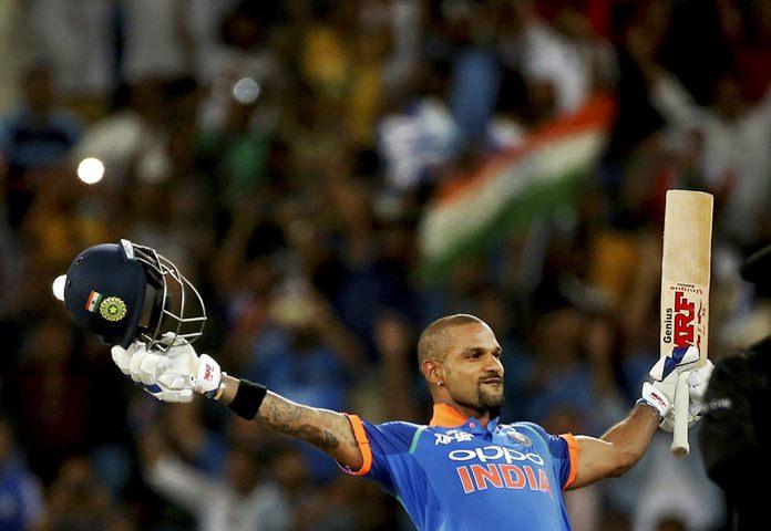 India's Shikhar Dhawan raises his bat and helmet to celebrate scoring a century during the one day international cricket match of Asia Cup between India and Pakistan in Dubai, United Arab Emirates, Sunday, Sept. 23. (AP Photo/Aijaz Rahi)