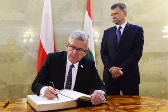 In this Monday, Sept. 12, 2016 file photo, Speaker of the Polish Senate Stanislaw Karczewski, left, signs the guest book after his meeting with Speaker of the Hungarian Parliament Laszlo Kover, right, in the Hungarian Parliament in Budapest, Hungary. (Tamas Kovacs/MTI via AP)