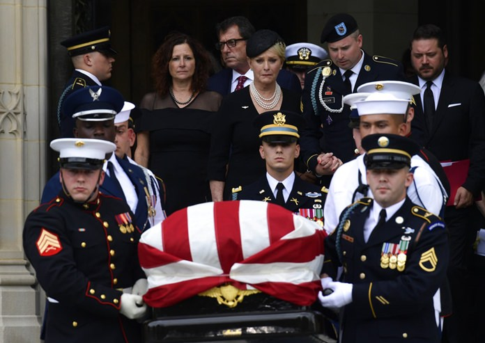 The casket of Sen. John McCain, R-Ariz., is carried out of the Washington National Cathedral in Washington, Saturday, Sept. 1, 2018, after a memorial service, as Cindy McCain is escorted by her son Jimmy McCain and other family members. (AP Photo/Susan Walsh)