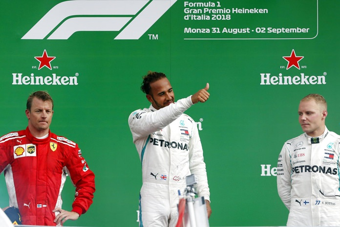 Mercedes driver Lewis Hamilton of Britain, center, celebrates on the podium with his teammate Mercedes driver Valtteri Bottas of Finland, right, and Ferrari driver Kimi Raikkonen of Finland after winning the Formula One Italy Grand Prix at the Monza racetrack, in Monza, Italy, Sunday, Sept. 2, 2018. (AP Photo/Antonio Calanni)