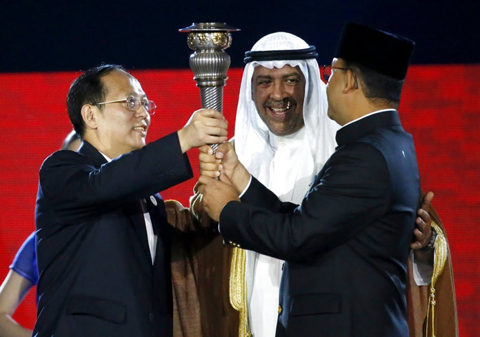 China's Olympic Committee chairman Gou Zhongwen, left, receives the torch from Governor of Jakarta Anies Baswedan, right, as Olympic Council of Asia president Sheikh Ahmad al-Fahad al-Sabah, centre, watches during the closing ceremony for the 18th Asian Games in Jakarta, Indonesia, Sunday, Sept. 2, 2018. (AP Photo/Lee Jin-man)