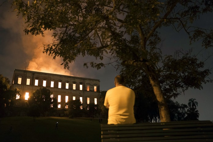 A man watches as flames engulf the 200-year-old National Museum of Brazil, in Rio de Janeiro, Sunday, Sept. 2, 2018. According to its website, the museum has thousands of items related to the history of Brazil and other countries. The museum is part of the Federal University of Rio de Janeiro. (AP Photo/Leo Correa)