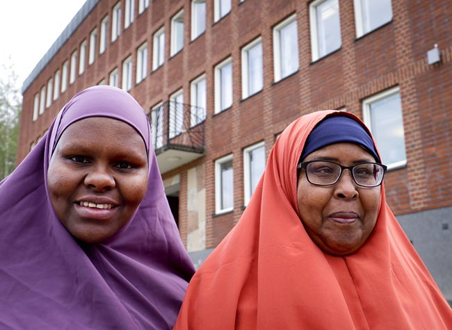 In this Aug. 30, 2018 photo Marian Omar, left, and Anab Adan, both from Somalia, pose in front of the town hall in Flen, some 100 km west of Stockholm, Sweden. The town has welcomed so many asylum seekers in recent years that they now make up about a fourth of the population. (AP Photo/Michael Probst)