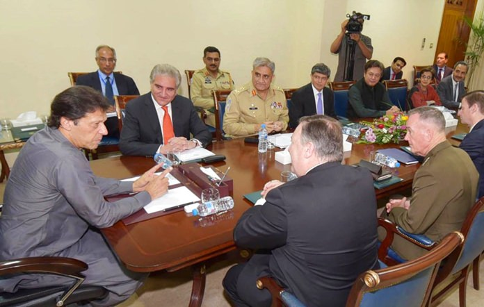 In this photo released by Press Information Department, Pakistan's Prime Minister Imran Khan, left, meets visiting U.S. Secretary of State Mike Pompeo, front, in Islamabad, Pakistan, Wednesday, Sept. 5, 2018. (Press Information Department via AP)