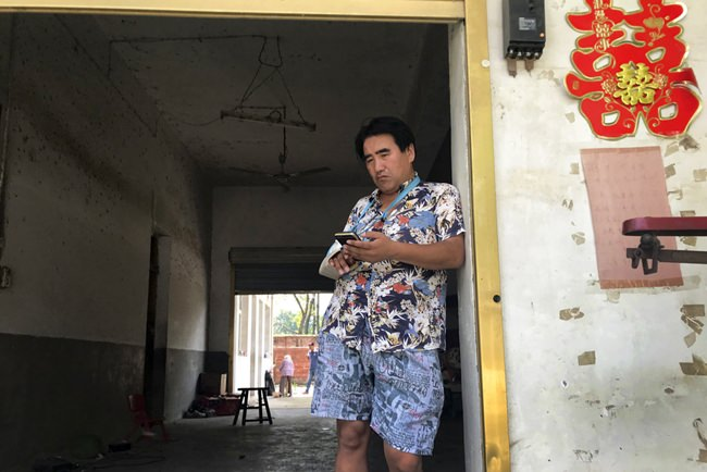 "In this July 12, 2018, photo, Li Qinggong stands outside the entrance to this home in Gucheng village in central China's Henan province. The AP spoke to the family Marip Lu, a young woman from Myanmar, accused of abusing her. The father, Li Qinggong, and mother, Xu Ying, both denied Marip Lu had been abused or raped, and insisted she had not been purchased. But neither was able to explain how she'd ended up in their faraway village, or how she allegedly met and ""married"" their mentally disabled son, Li Mingming. (AP Photo/Ng Han Guan)"