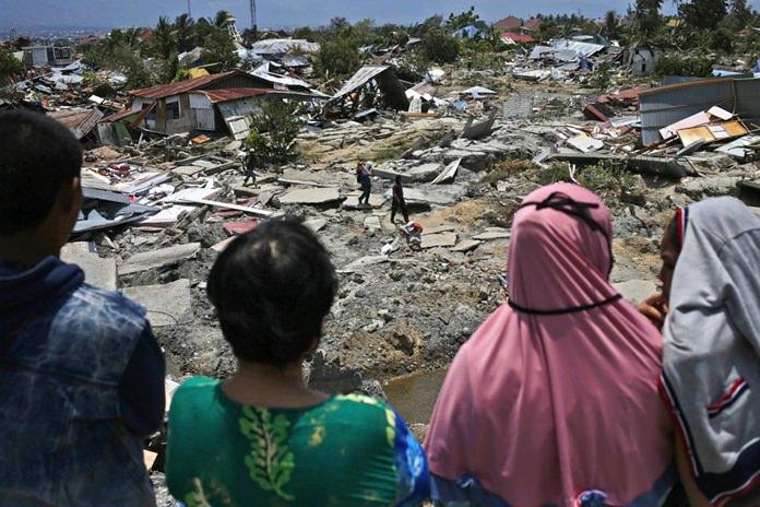 Women survey the damage suffered by Balaroa neighborhood which was flattened by Friday's earthquake in Balaroa neighborhood in Palu, Central Sulawesi, Indonesia Tuesday, Oct. 2. (AP Photo/Dita Alangkara)