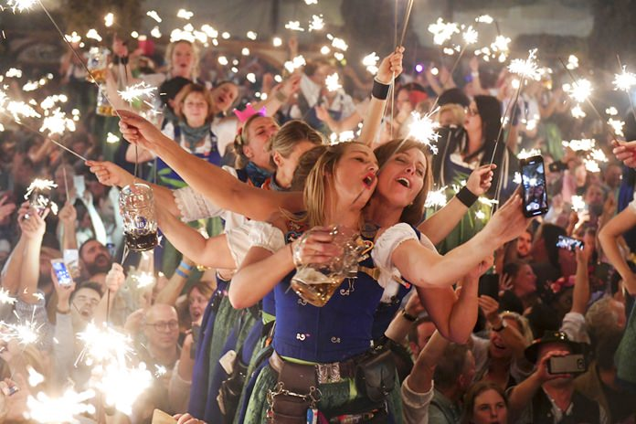 In this Oct. 7, 2018 photo waitresses dance in the Hofbraeu tent after the closing of the Oktoberfest beer festival in Munich, southern Germany. (Felix Hoerhager/dpa via AP)