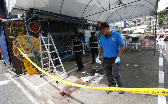 A police forensics team investigates a shooting scene where one tourist was killed in Bangkok, Monday, Oct. 8. (AP Photo/Sakchai Lalit)