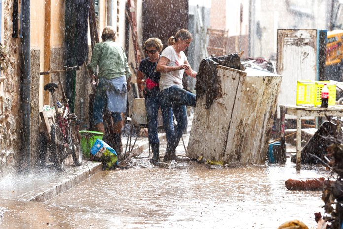 Residents place their damaged belongings on the street under pouring rain, in Sant Llorenc, 60 kilometers east of Mallorca's capital, Palma, Spain, Wednesday, Oct. 10. (AP Photo/Francisco Ubilla)