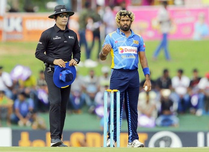 Sri Lanka's Lasith Malinga sets the field as umpire Richira Palliyaguru watches during their first one-day international cricket match with England in Dambulla, Sri Lanka, Wednesday, Oct. 10. (AP Photo/Eranga Jayawardena)