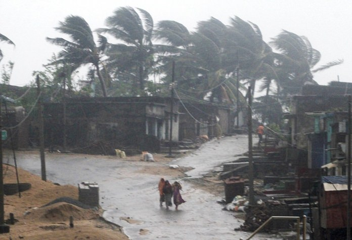 Indian villagers walk towards a shelter near Arjipalli beach during rain and strong winds caused by cyclonic storm named Titli, or Butterfly near Gopalpur on the Bay of Bengal coast, Ganjam district, eastern Orissa state, India, Thursday, Oct.11. (AP Photo)