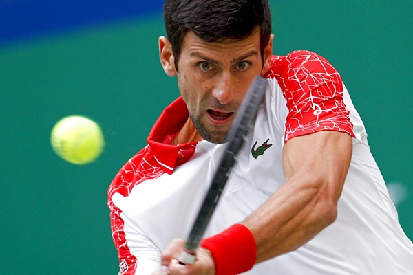 Novak Djokovic of Serbia hits a return shot to Marco Cecchinato of Italy during their men's singles match of the Shanghai Masters tennis tournament at Qizhong Forest Sports City Tennis Center in Shanghai, China, Thursday, Oct. 11. (AP Photo/Andy Wong)