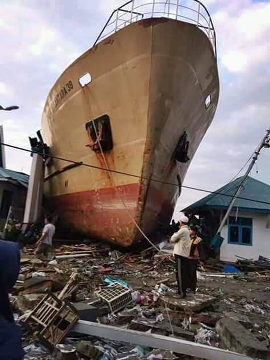 In this Saturday, Sept. 29, 2018, photo, villagers view a ship swept ashore by a tsunami in Palu, Central Sulawesi, Indonesia. (AP Photo/Rio Mario, File)