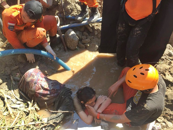 An Indonesia rescue team evacuates a women from damage, Sunday, Sept. 30. (AP Photo/Chandra)