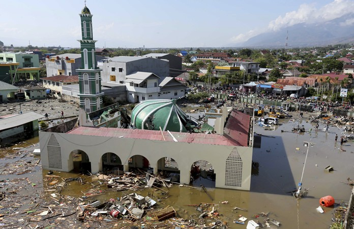 In this Sunday, Sept. 30, 2018, photo, people survey the mosque damaged in a massive earthquake and a tsunami. (AP Photo/Tatan Syuflana, File)