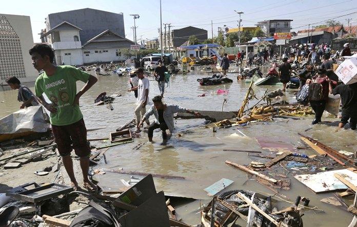 People survey the damage of a shopping mall following the earthquakes and a tsunami in Palu. (AP Photo/Tatan Syuflana, File)