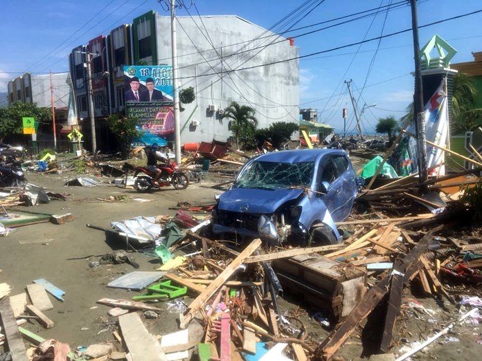 A motorbike passes the wreckage of a car following earthquakes and a tsunami in Palu, Central Sulawesi, Indonesia, Sunday, Sept. 30. (AP Photo/Tatan Syuflana)