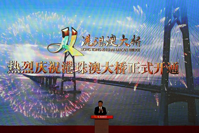 Chinese President Xi Jinping applauds on stage during the official opening of the China-Zhuhai-Macau-Hong Kong Bridge Tuesday, Oct. 23, 2018. (AP Photo/Andy Wong)