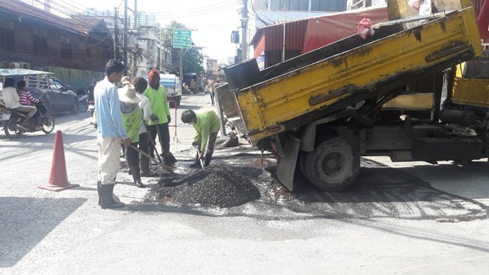 Workers patch potholes outside the Amorn Market following complaints from vendors and shoppers.