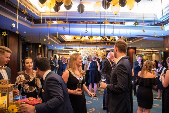 Guests enjoy cocktails under golden stars and balloons before the main event.