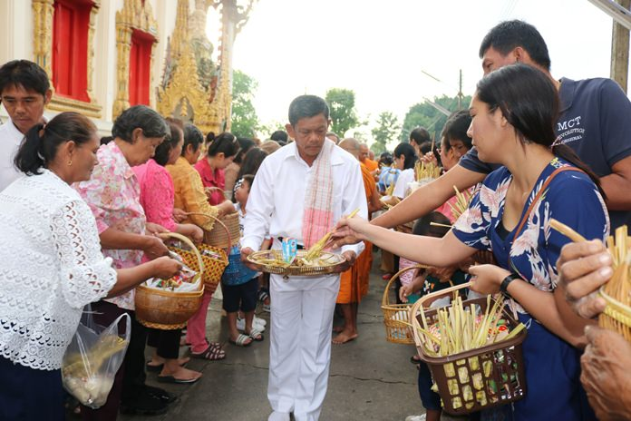 People make merit by presenting alms at Wat Suttawas.