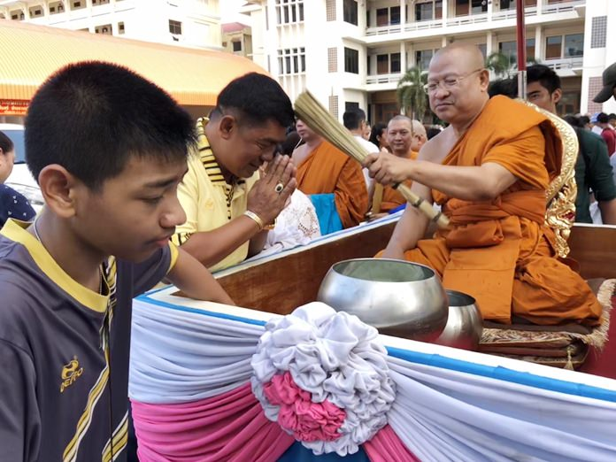 Tan Jao Khun Panya Rattanaporn, Abbot of Wat Chaimongkol Royal Temple sprinkles holy water on disciples.
