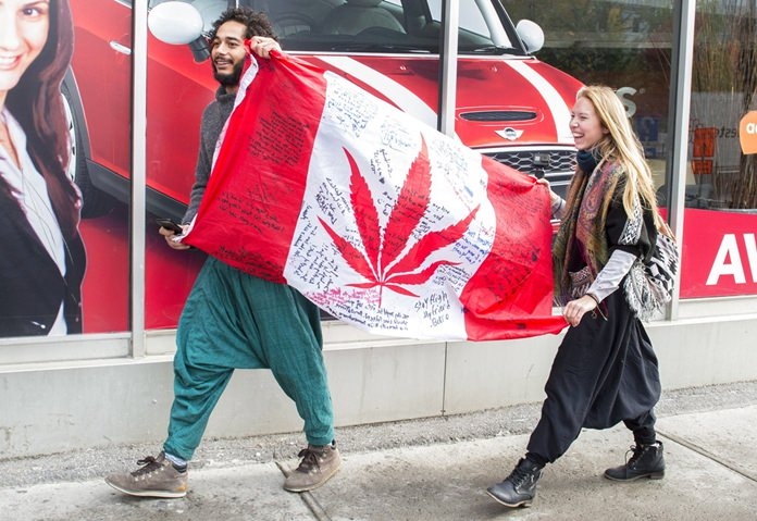 People hold up a Canadian flag with a marijuana logo on it outside a government cannabis store in Montreal, Wednesday, Oct. 17. Canada became the largest country with a legal national marijuana marketplace as sales began early Wednesday. (Graham Hughes/The Canadian Press via AP)