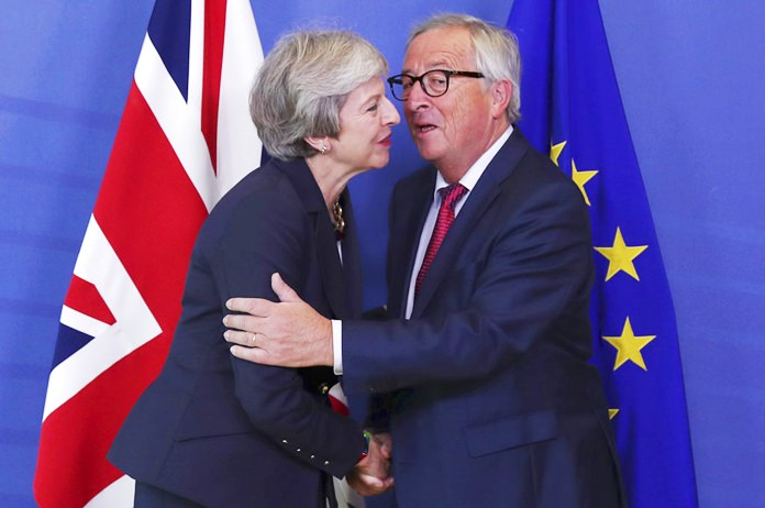 British Prime Minister Theresa May, left, hugs Jean-Claude Juncker, President of the European Commission, as they meet in Brussels, Wednesday, Oct. 17. (AP Photo/Francisco Seco)