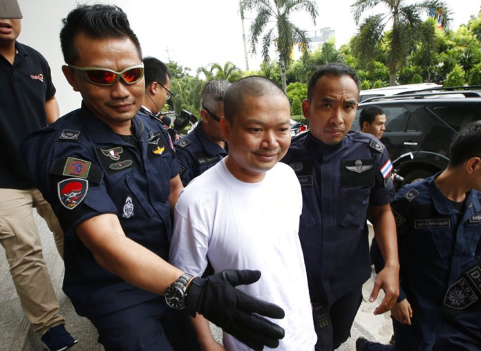 In this Thursday, July 20, 2017 file photo, ex-monk Wirapol Sukphol is escorted by the Department of Special Investigation officials to the prosecutor's office in Bangkok. (AP Photo/Sakchai Lalit)